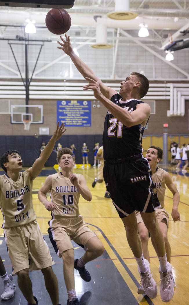 Moapa Valley senior center Josh Cox (21) drives baseline past Boulder City junior guard Gavin Balistere (10) and senior guard Tre Hershey (5) in the second quarter on Tuesday, Jan. 29, 2019, at Bo ...