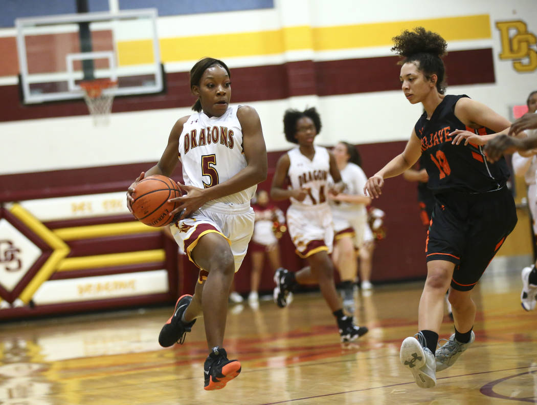 Del Sol's Markay Merchant (5) drives to the basket past Mojave's Ta'nyia Zeno (10) during the first half of a basketball game at Del Sol High School in Las Vegas on Wednesday, Jan. 30, 2019. (Chas ...