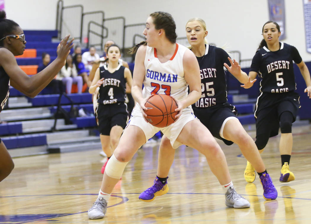 Bishop Gorman's Tierney Holcombe (23) moves the ball around Desert Oasis' Melissa Simmons (25) during the first half of a basketball game at Bishop Gorman High School in Las Vegas on Friday, Feb. ...