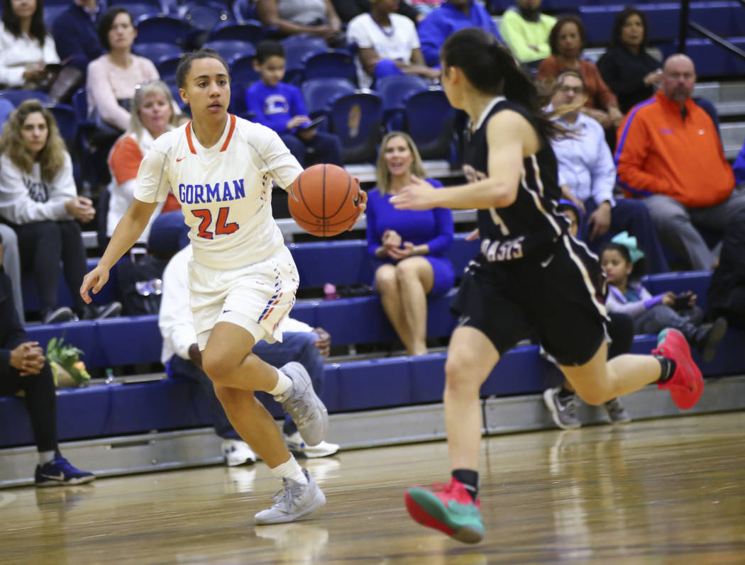 Bishop Gorman's Bentleigh Hoskins (24) brings the ball up court against Desert Oasis' Brianna Clark (4) during the first half of a basketball game at Bishop Gorman High School in Las Vegas on Frid ...
