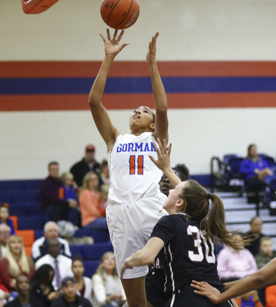 Bishop Gorman's Olivia Smith (11) shoots past Desert Oasis' Sierra Mich'l (30) during the first half of a basketball game at Bishop Gorman High School in Las Vegas on Friday, Feb. 1, 2019. (Chase ...