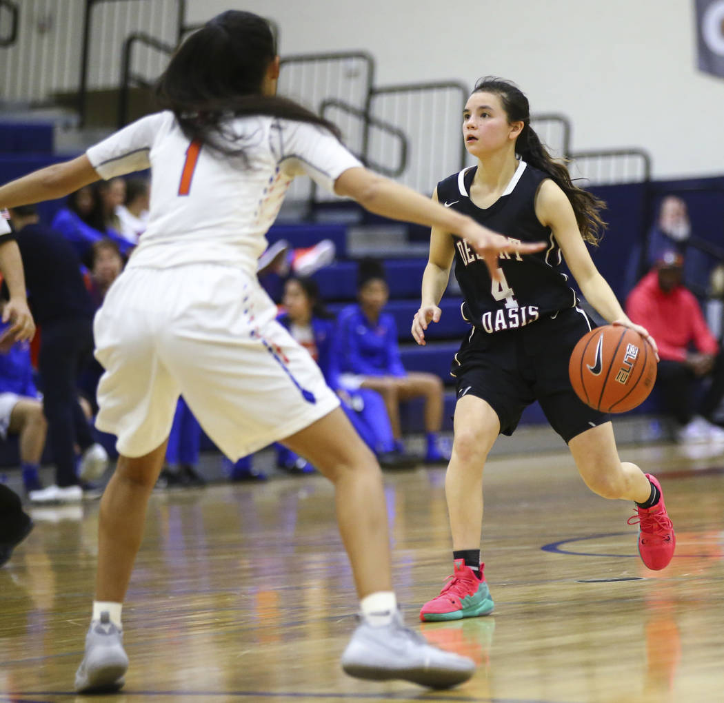 Desert Oasis' Brianna Clark (4) brings the ball up court against Bishop Gorman's Caira Young (1) during the second half of a basketball game at Bishop Gorman High School in Las Vegas on Friday, Fe ...