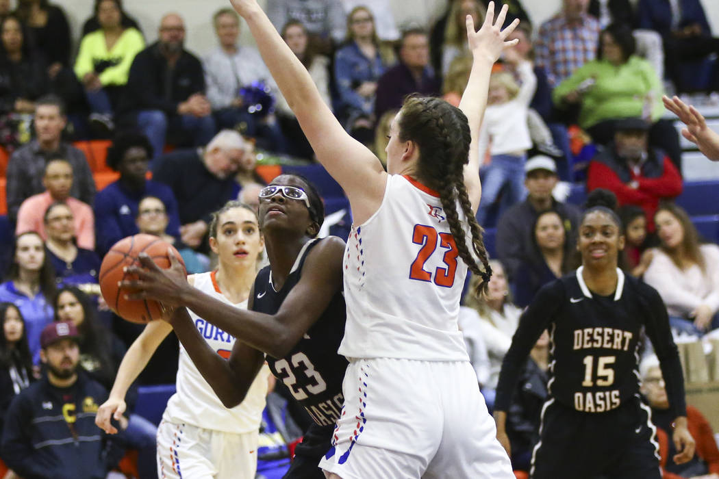Desert Oasis' Desi-Rae Young, left, looks to shoot against Bishop Gorman's Tierney Holcombe during the second half of a basketball game at Bishop Gorman High School in Las Vegas on Friday, Feb. 1, ...