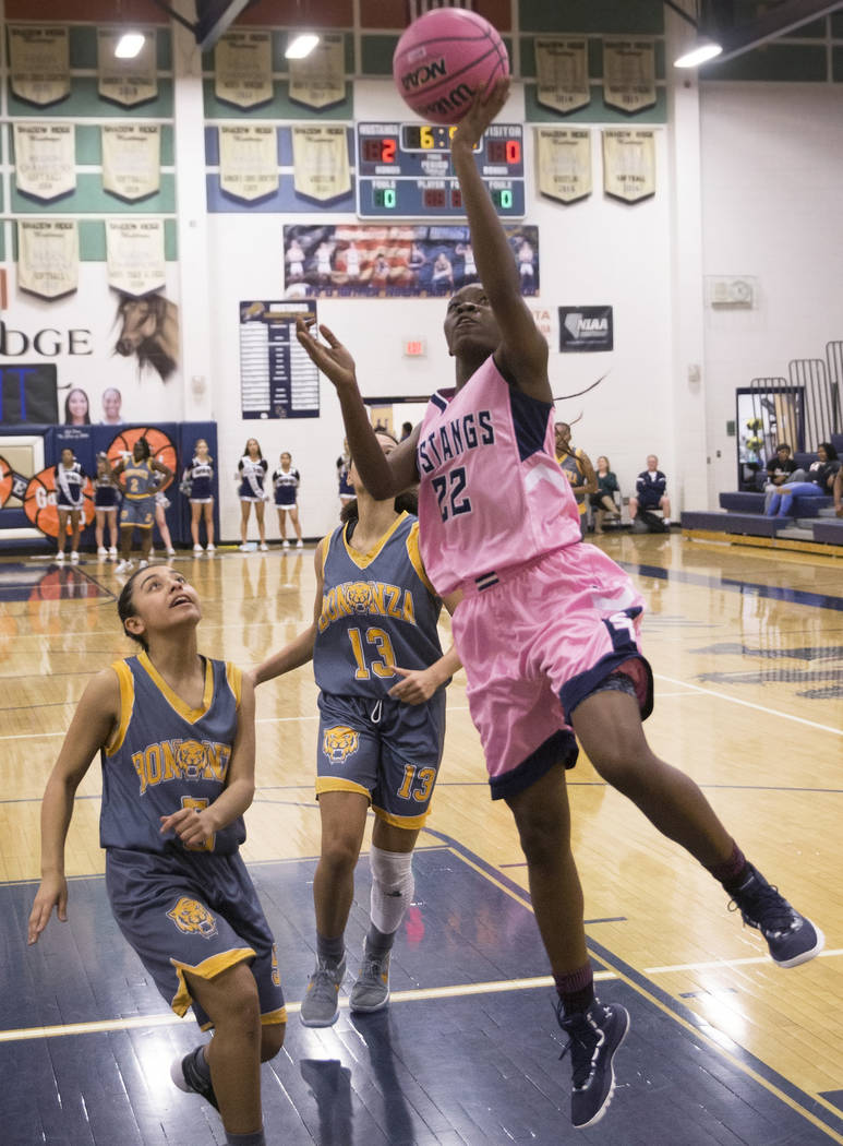 Shadow Ridge senior Vashay Young (22) converts a fast break layup over Bonanza senior Macyn Raleigh (13) and sophomore Isaira Diaz (5) in the first quarter on Monday, Feb. 4, 2019, at Shadow Ridge ...