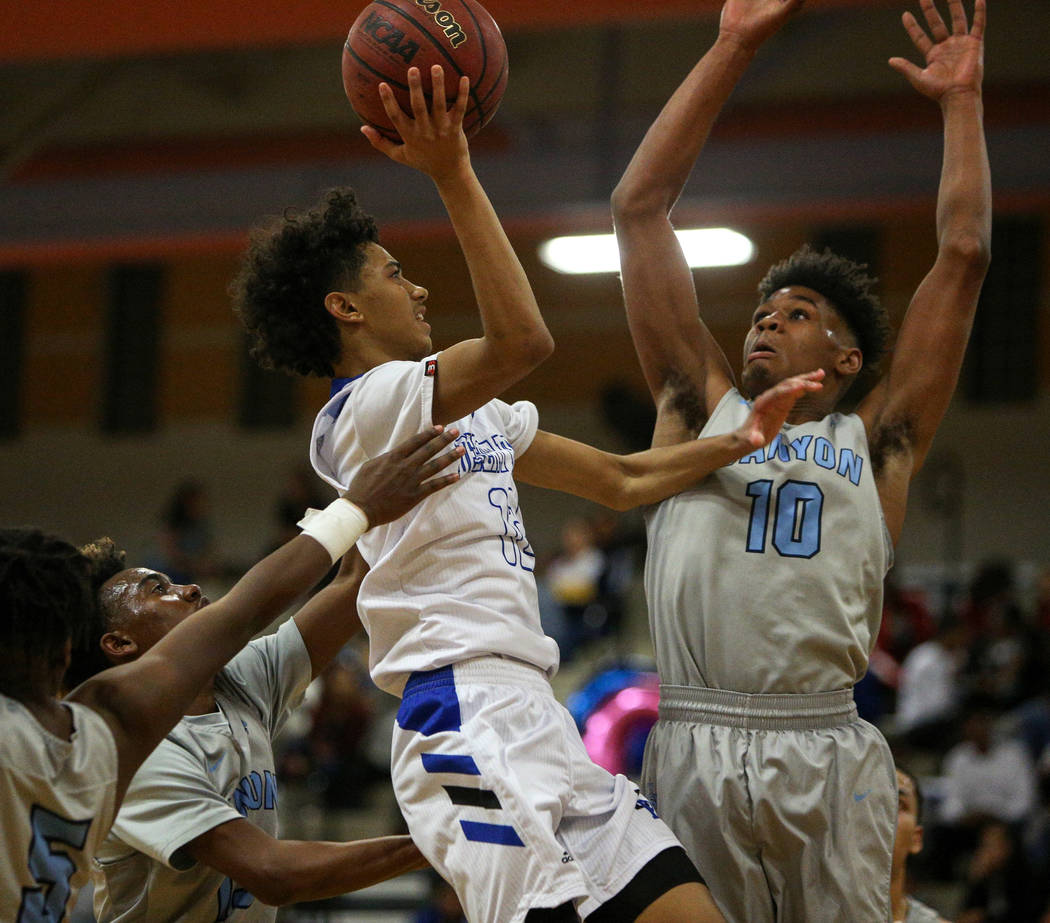 Desert Pines' Milos Uzan (12) jumps up to take a shot while under pressure from Canyon Springs' Christoper Ward (10) during a basketball game at Desert Pines High School in Las Vegas, Tuesday, Feb ...