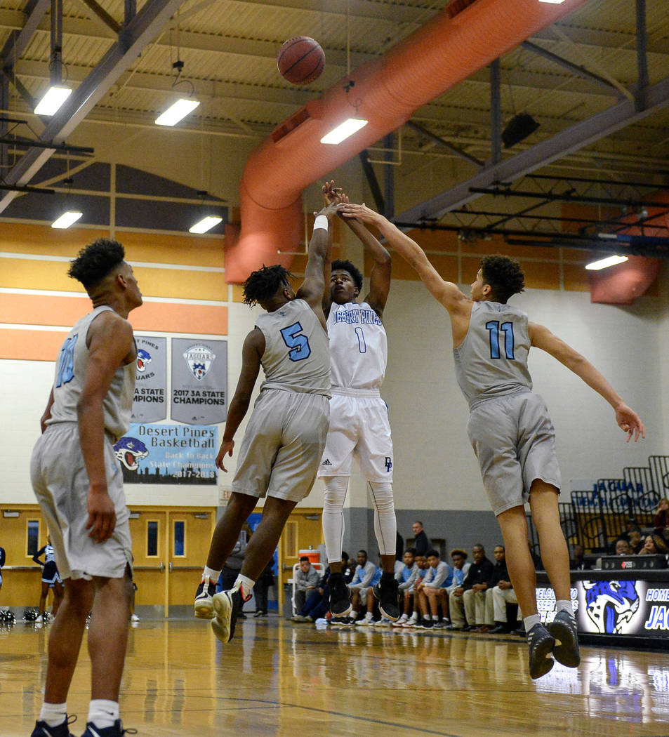 Desert Pines' Semaj Threats (1) jumps up to take a shot while under pressure from Canyon Springs' Tommie Anderson (5), left, and Kayvon Alexander (11) during a basketball game at Desert Pines High ...