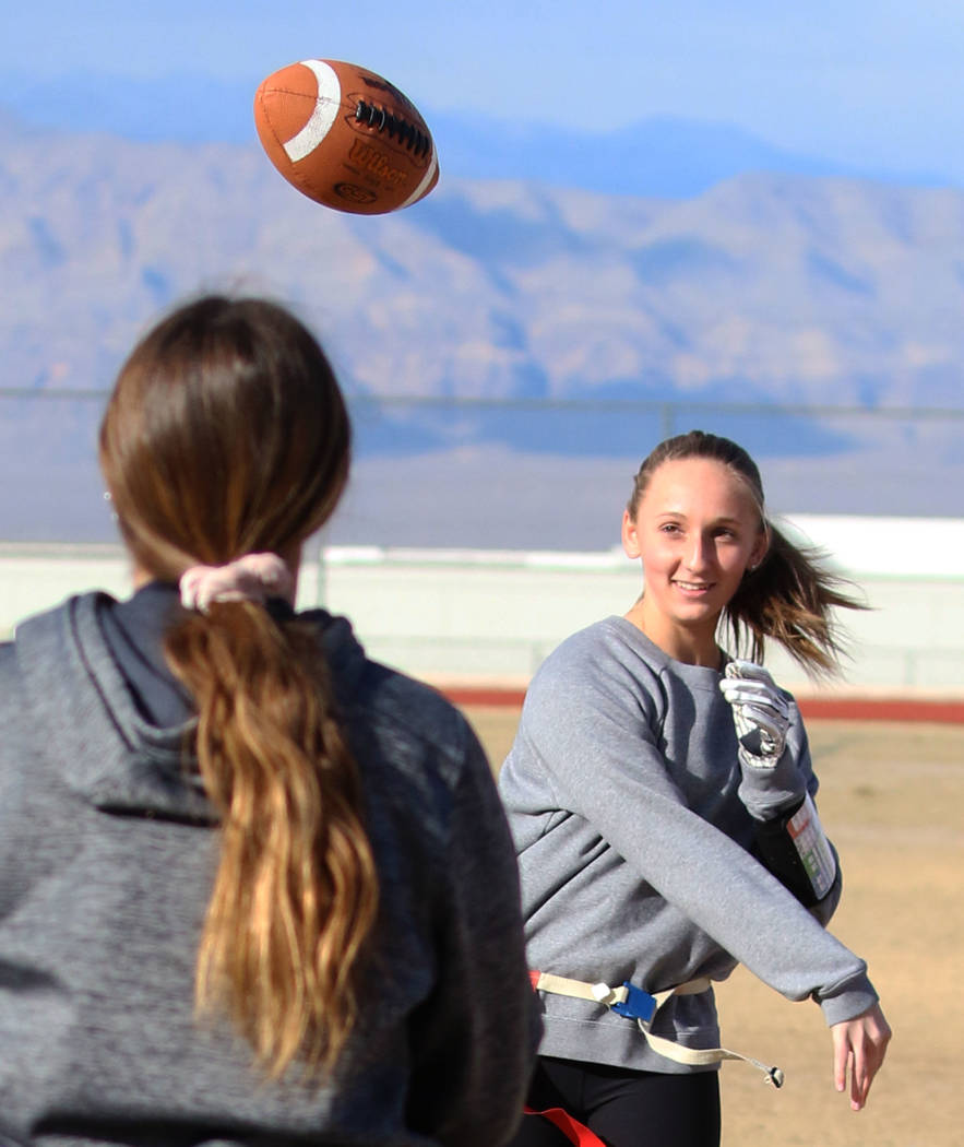 Coronado freshman flag football quarterback Ashtyn Almeido throws the ball to backup quarterback Kaylin Hall as they warm up during team practice on Wednesday, Feb. 6, 2019, at Coronado High Schoo ...
