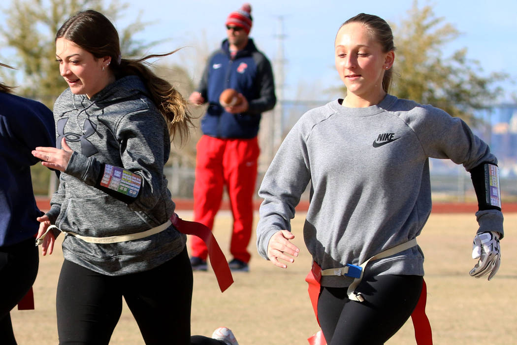 Coronado flag football quarterbacks Ashtyn Almeido, right, and Kaylin Hall, sprint as head coach Rusty Andersen, center, looks on during team practice on Wednesday, Feb. 6, 2019, at Coronado High ...