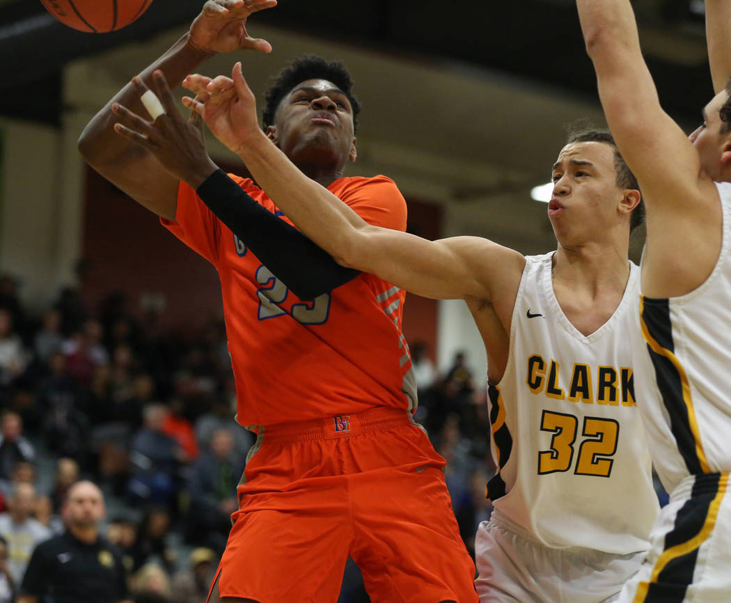 Bishop Gorman's Mwani Wilkinson (23) gets the ball knocked out of his possession by Clark's Ian Alexander (32) during a basketball game at Clark High School in Las Vegas, Thursday, Feb. 7, 2019. C ...