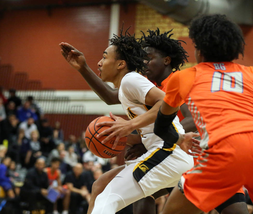 Clark's Frankie Collins (1) drives past Bishop Gorman's Zaon Collins (10), front, and Will McClendon (1) during a basketball game at Clark High School in Las Vegas, Thursday, Feb. 7, 2019. Carolin ...
