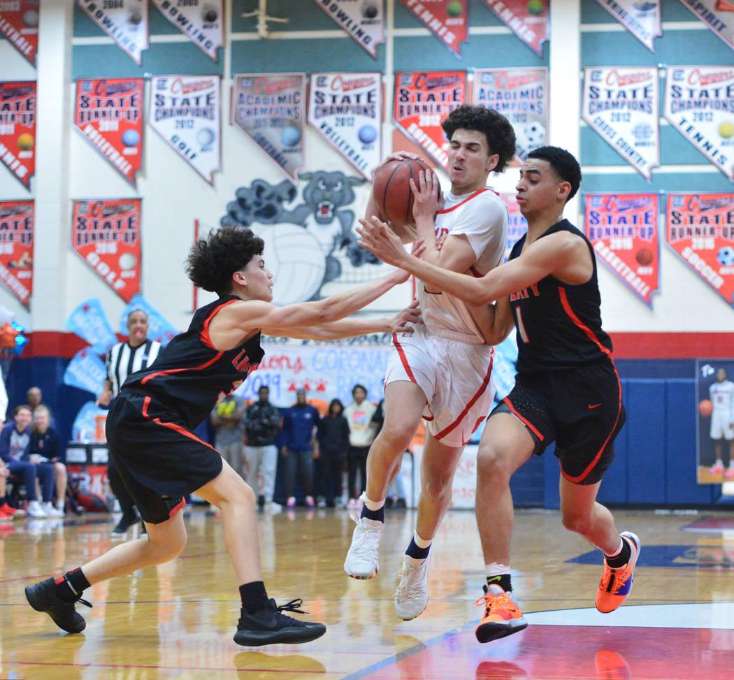 Coronado's Richard Issacs (2) drives between Liberty's Lorenzo Abellar (3) and Liberty's Kobe Stroughter (1) during a game between Coronado High School and Liberty High School at Coronado High Sch ...