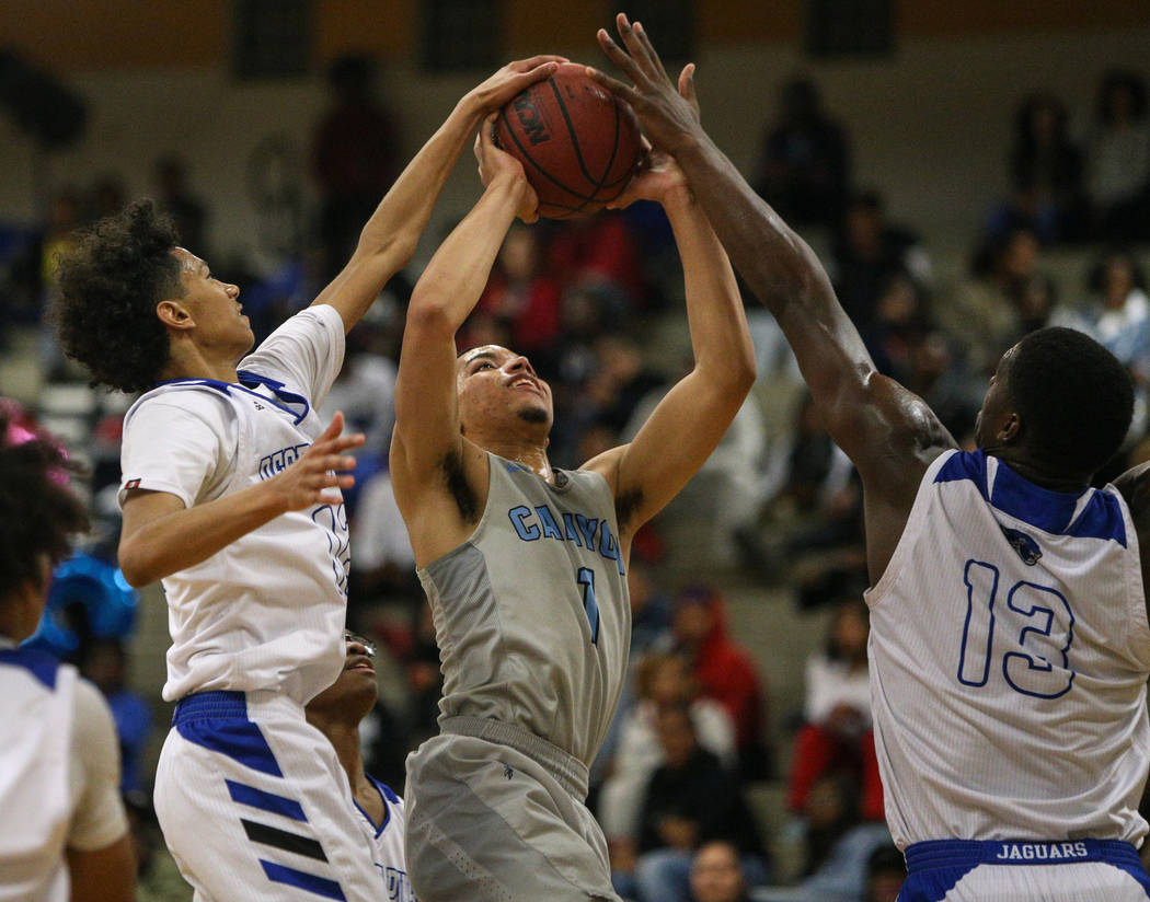 Canyon Springs' Mervin Soares (1) attempts to take a shot while Desert Pines' Milos Uzan (12), left, and Darnell Washington (13) block the shot during a basketball game at Desert Pines High School ...