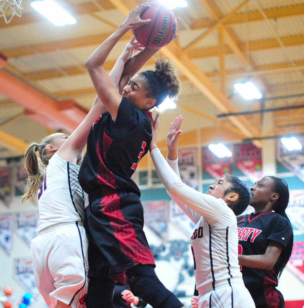 Liberty senior Journie Augmon (3) pulls down a rebound over Coronado senior Kaitlyn Hamlin (31) in the fourth quarter of a game between Coronado High School and Liberty High School at Coronado Hig ...