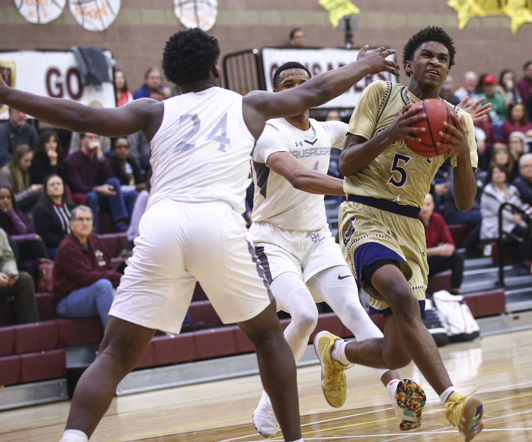 Cheyenne's Glenn Taylor (5) drives to the basket past Faith Lutheran's D.J. Heckard (24) during the second half of a basketball game at Faith Lutheran High School in Las Vegas on Wednesday, Feb. 1 ...