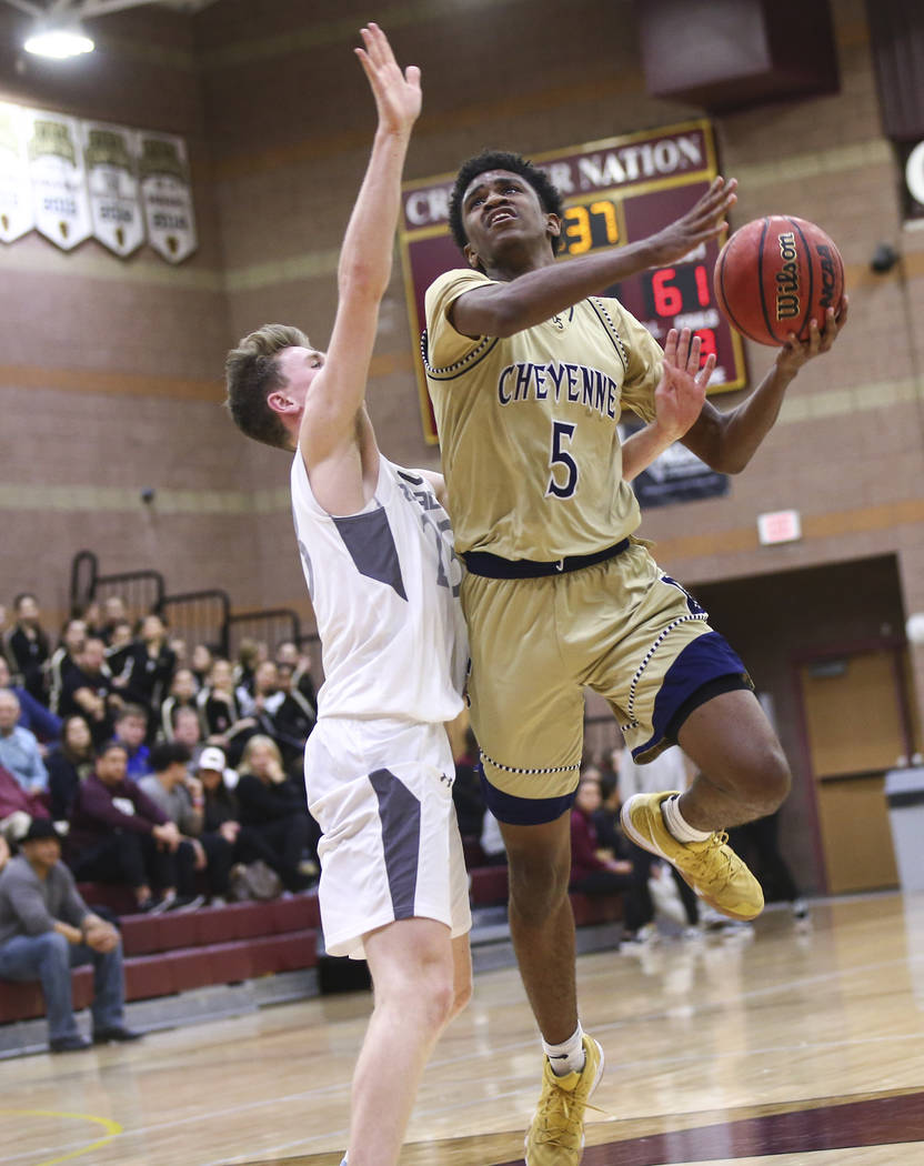 Cheyenne's Glenn Taylor (5) mvoes the ball around Faith Lutheran's Brevin Walter (23) during the second half of a basketball game at Faith Lutheran High School in Las Vegas on Wednesday, Feb. 13, ...