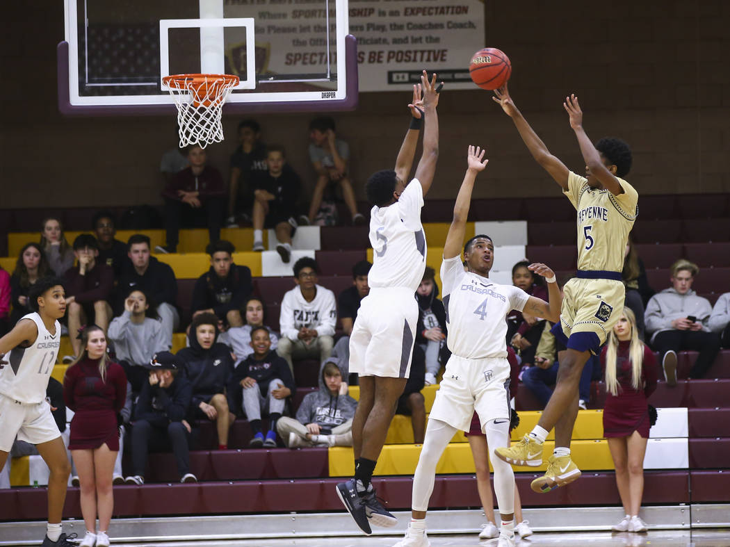 Cheyenne's Glenn Taylor (5) shoots over Faith Lutheran's Azavier Johnson (5) and Sedrick Hammond (4) during the first half of a basketball game at Faith Lutheran High School in Las Vegas on Wednes ...