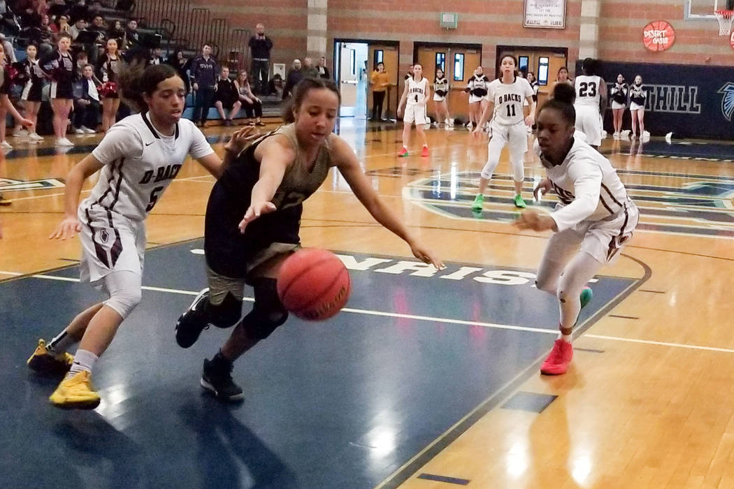 Spring Valley's Garrisen Freeman, center, battles for a loose ball with Desert Oasis' Eliyjah Pricebrooks, left, and Ahmaya Smith during the Desert Region semifinals on Tuesday, Feb. 19, 2019 at F ...