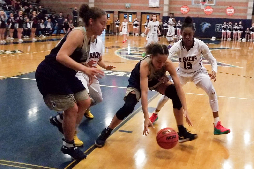 Spring Valley's Garrisen Freeman tries to scoop up a loose ball as Desert Oasis' Ahmaya Smith (15) defends during the Desert Region semifinals on Tuesday, Feb. 19, 2019 at Foothill. (Damon Seiters ...