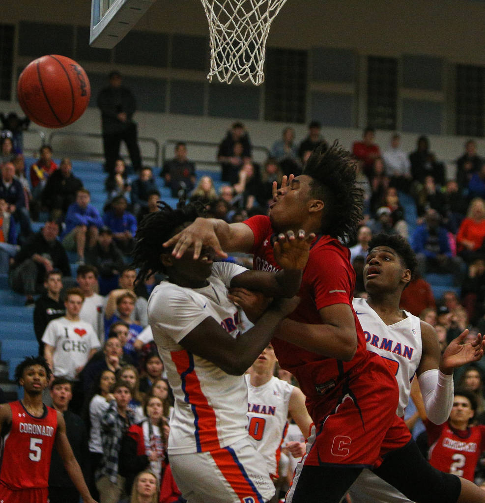 Bishop Gorman's Will McClendon (1) swats the ball out of the hands of Coronado's Jhaylon Martinez (33) during the Desert Region boys semifinal game at Foothill High Schoo in Henderson, Tuesday, Fe ...