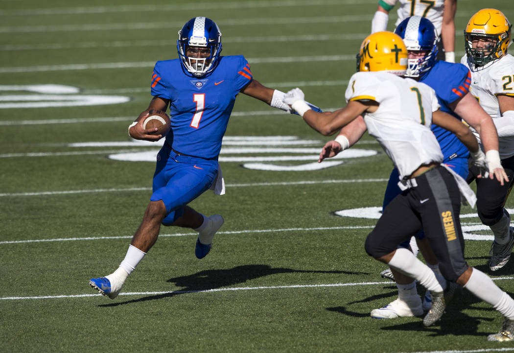 Bishop Gorman quarterback Micah Bowens (1) runs the ball against Bishop Manogue's Elijah Lee (1) during the first half of the NIAA high school football championship at Sam Boyd Stadium in Las Vega ...