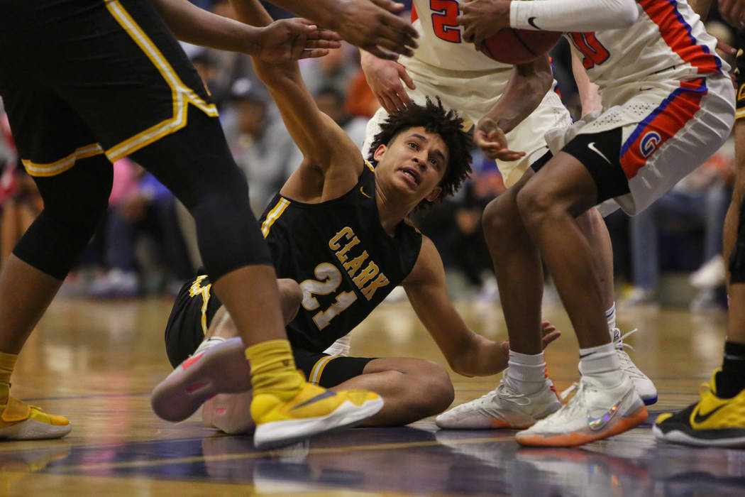 Clark's Jalen Hill (21) reaches for the ball after being knocked down during the first half of a basketball game at Bishop Gorman High School in Las Vegas, Monday, Jan. 14, 2019. Caroline Brehman/ ...