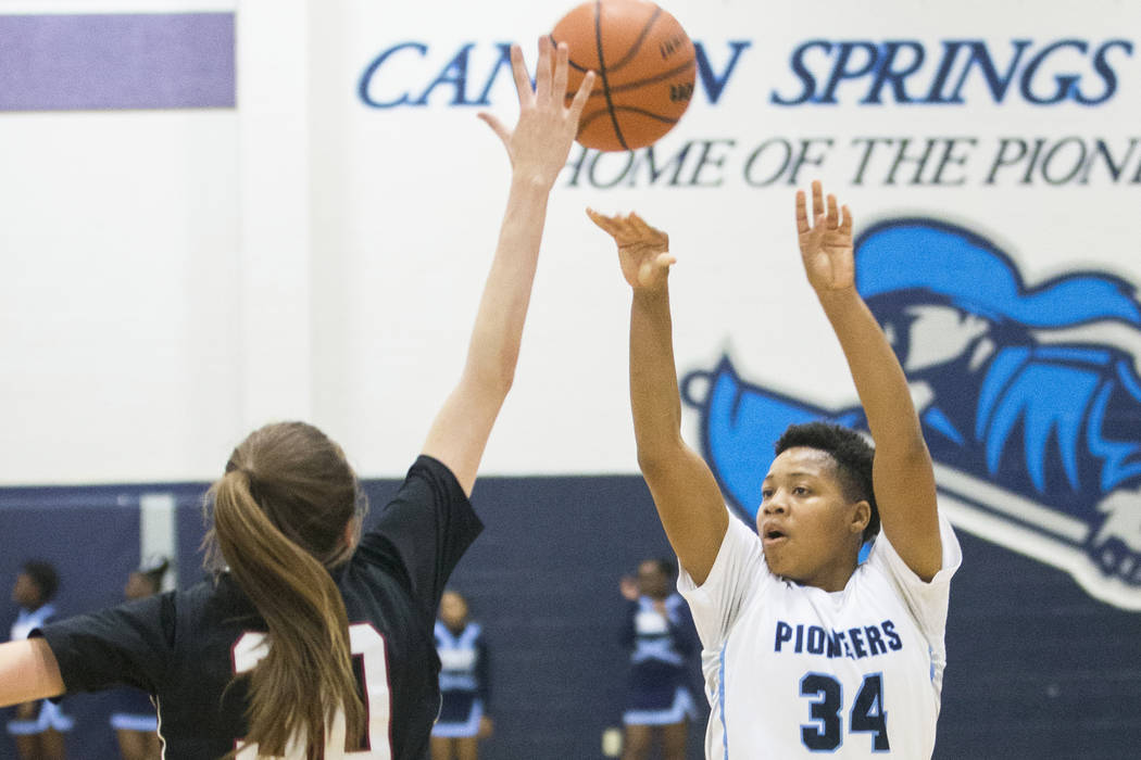 Canyon Springs junior forward Ja'moni Brown (34) shoots a jump shot over Desert Oasis senior forward Sierra Mich'l (30) in the second quarter on Friday, Jan. 18, 2019, at Canyon Springs High Schoo ...
