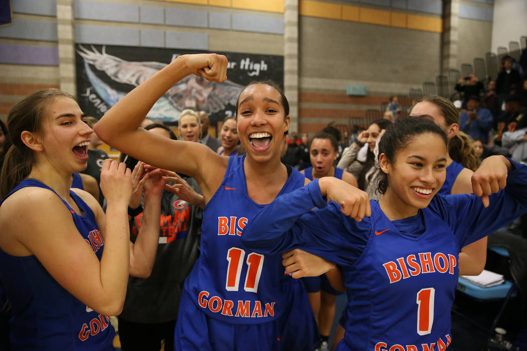 Bishop Gorman's Lexi Kruljac (22), Olivia Smith (11) and Caira Young (1), celebrate their win against Desert Oasis in the Desert Region girls basketball championship game at Foothill High School i ...