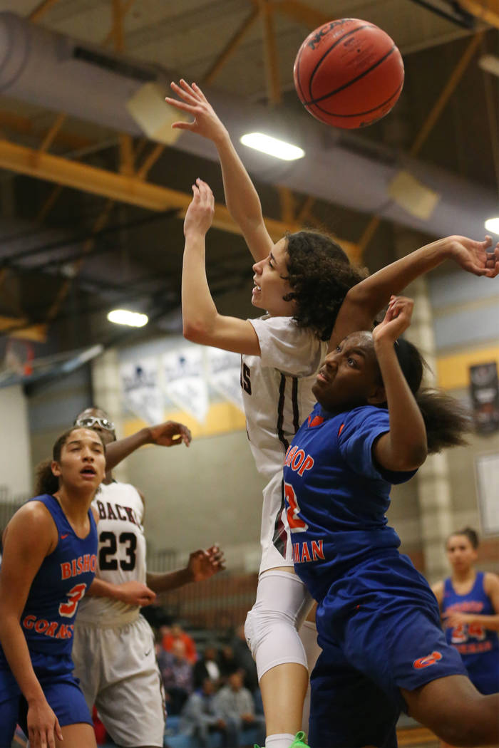 Bishop Gorman's Aaliyah Bey (12) blocks a shot by Desert Oasis' Eliyjah Pricebrooks (5) in the Desert Region girls basketball championship game at Foothill High School in Henderson, Saturday, Feb. ...