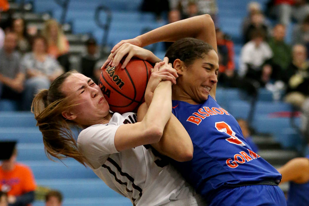 Desert Oasis' Sierra Mich'l (30) fights for the ball against Bishop Gorman's Georgia Ohiaeri (3) in the Desert Region girls basketball championship game at Foothill High School in Henderson, Satur ...
