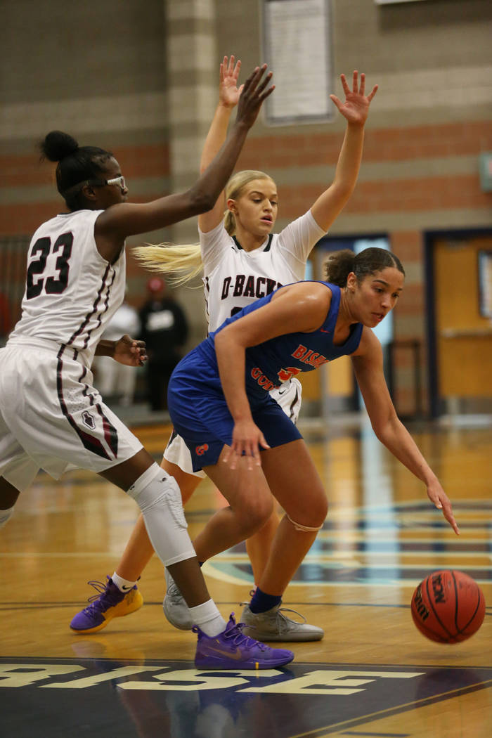 Bishop Gorman's Georgia Ohiaeri (3) looks to make a play under pressure from Desert Oasis' Desi-Rae Young (23) and Melissa Simmons (25) in the Desert Region girls basketball championship game at F ...