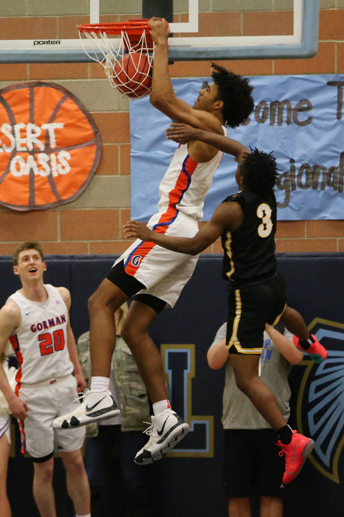 Bishop Gorman's Isaiah Cottrell (0) goes up for a dunk under pressure from Clark's Joel Burney (3) in the Desert Region boys basketball championship game at Foothill High School in Henderson, Satu ...