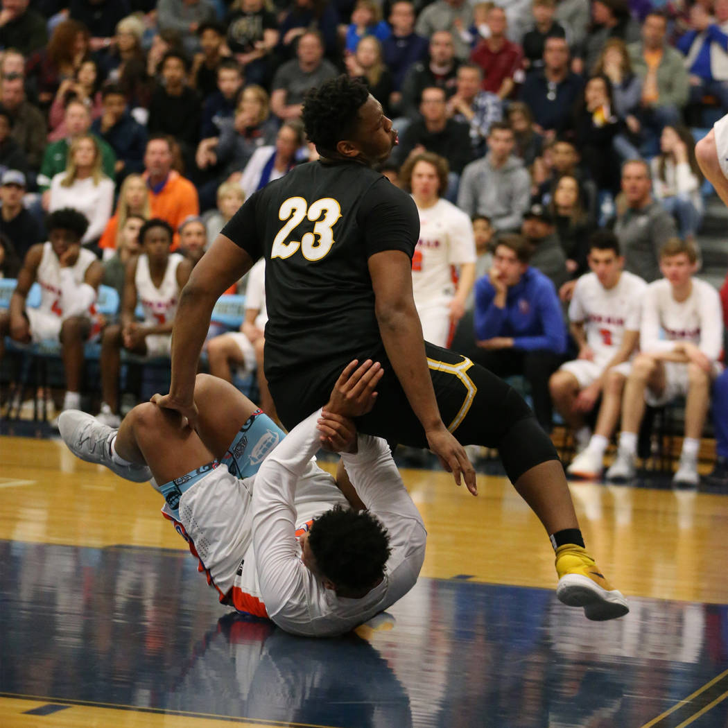 Clark's Antwon Jackson (23) falls over Bishop Gorman's Max Allen (12) in the Desert Region boys basketball championship game at Foothill High School in Henderson, Saturday, Feb. 23, 2019. Bishop G ...