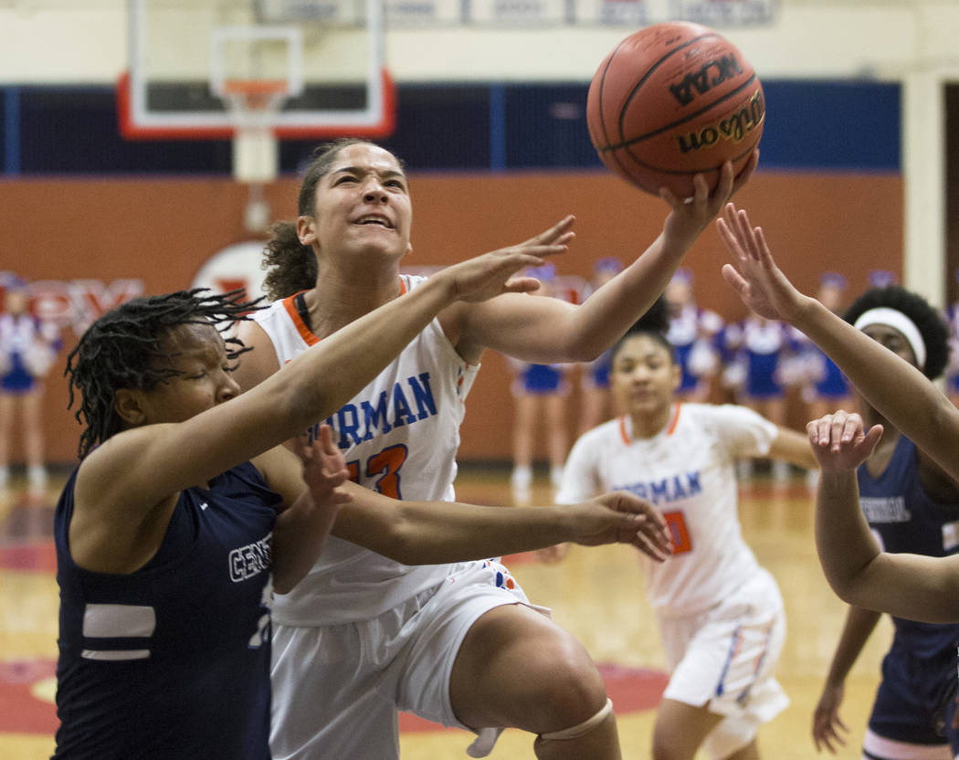 Bishop Gorman senior Georgia Ohiaeri (13) drives past Centennial junior Daejah Phillips (15) in the second quarter during the Southern Nevada girls basketball championship game on Monday, Feb. 25, ...