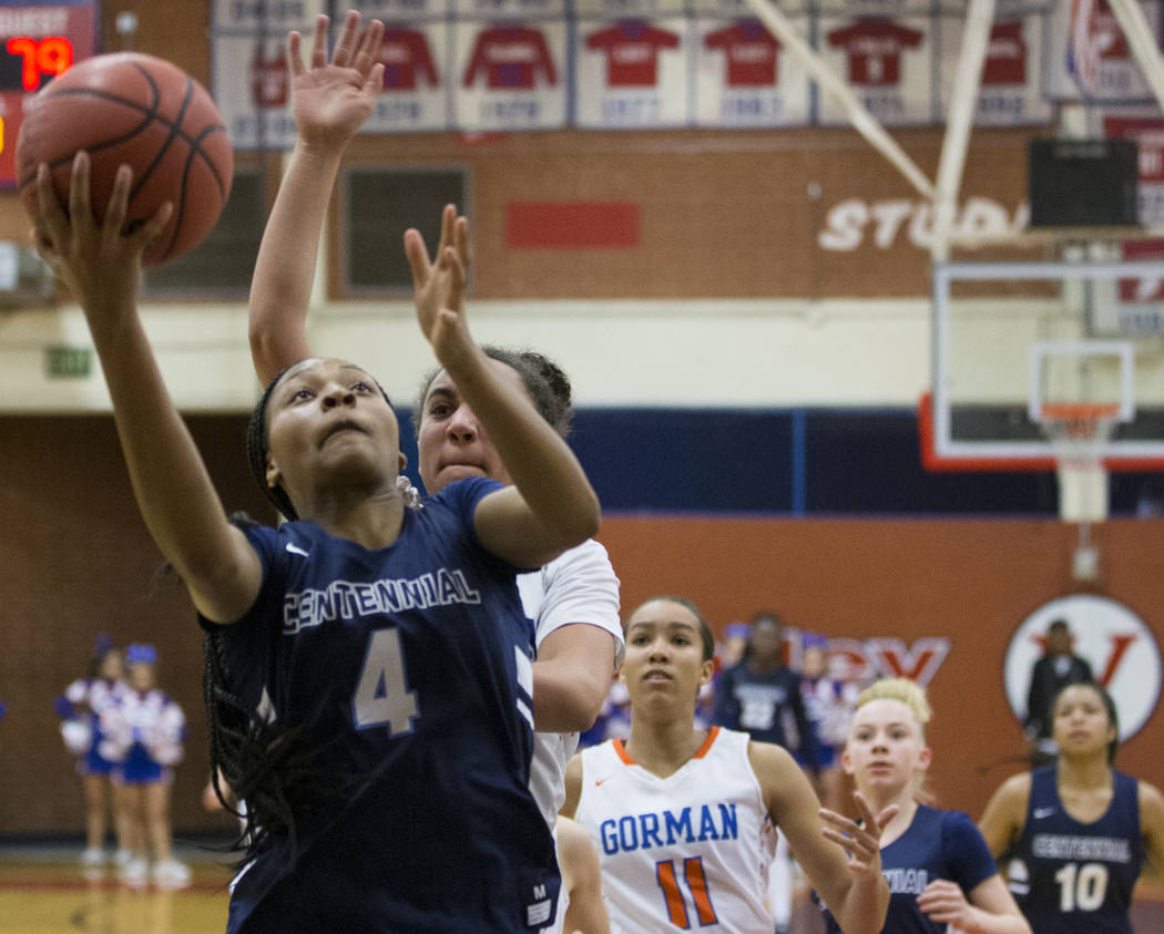 Centennial sophomore Taylor Bigby (4) drives past Bishop Gorman senior Olivia Smith (11) in the third quarter during the Southern Nevada girls basketball championship game on Monday, Feb. 25, 2019 ...