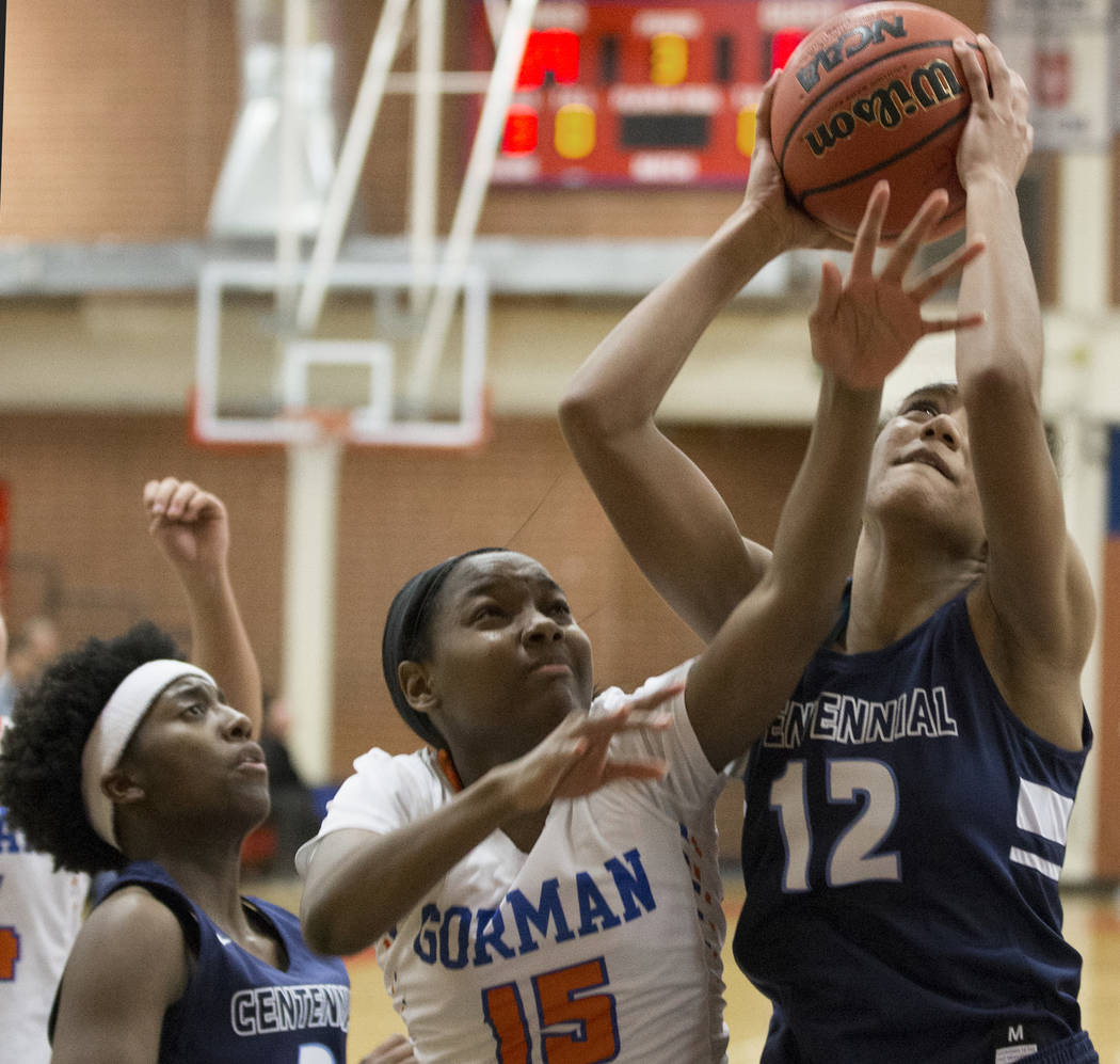 Centennial junior Aishah Brown (12) grabs a rebound over Bishop Gorman freshman Asya Bey (15) in the fourth quarter during the Southern Nevada girls basketball championship game on Monday, Feb. 25 ...
