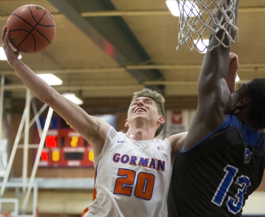 Bishop Gorman senior guard Noah Taitz (20) slices to the rim over Desert Pines junior Darnell Washington (13) in the second quarter during the Southern Nevada boys basketball championship game on ...