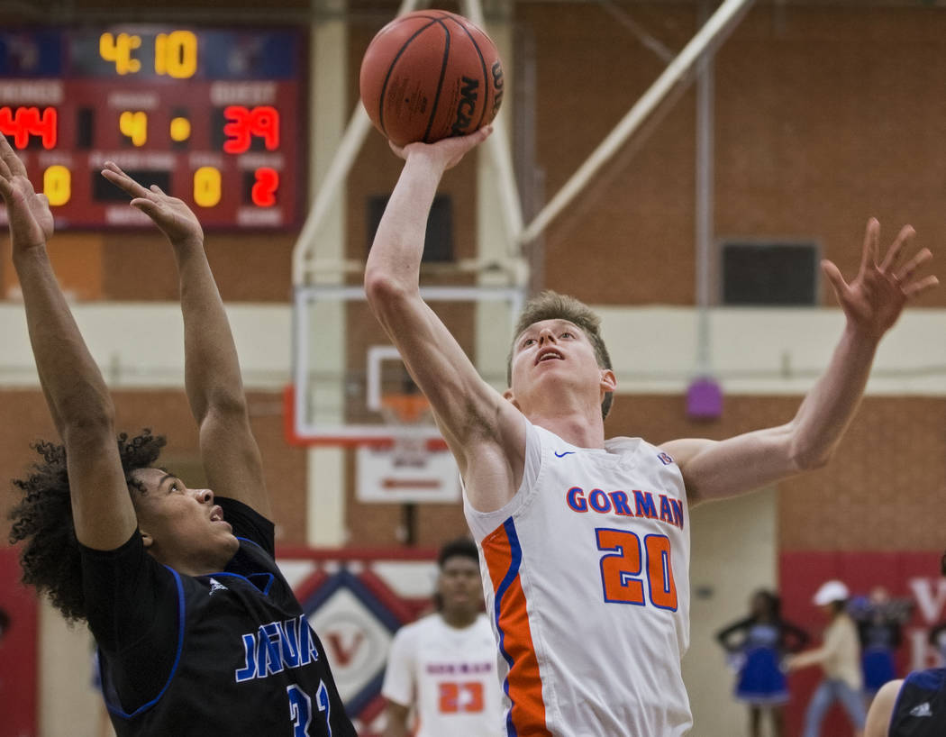Bishop Gorman senior guard Noah Taitz (20) drives past Desert Pines freshman Jamir Stephens (33) and sophomore Cimarron Conriquez (3) in the fourth quarter during the Southern Nevada boys basketb ...