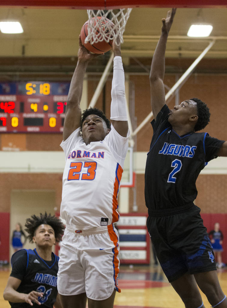 Bishop Gorman junior forward Mwani Wilkinson (23) drives past Desert Pines sophomore Dayshawn Wiley (2) in the third quarter during the Southern Nevada boys basketball championship game on Monday, ...