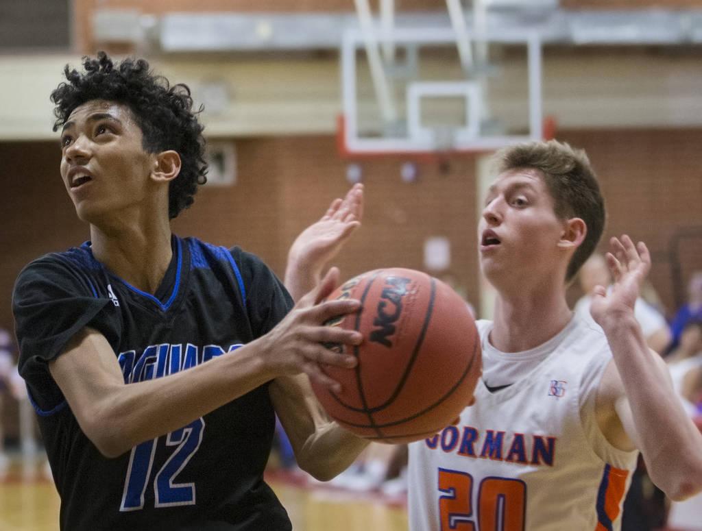 Desert Pines freshman Milos Uzan (12) drives past Bishop Gorman senior guard Noah Taitz (20) in the fourth quarter during the Southern Nevada boys basketball championship game on Monday, Feb. 25, ...