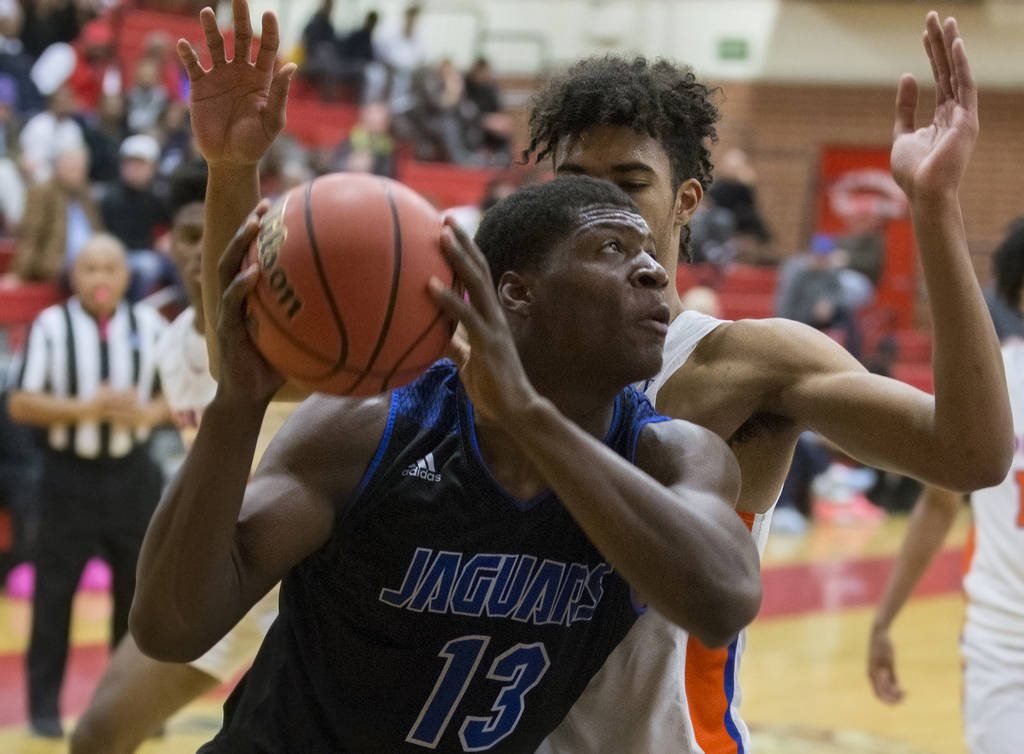 Desert Pines junior Darnell Washington (13) drives baseline past Bishop Gorman junior forward Isaiah Cottrell (0) in the fourth quarter during the Southern Nevada boys basketball championship game ...