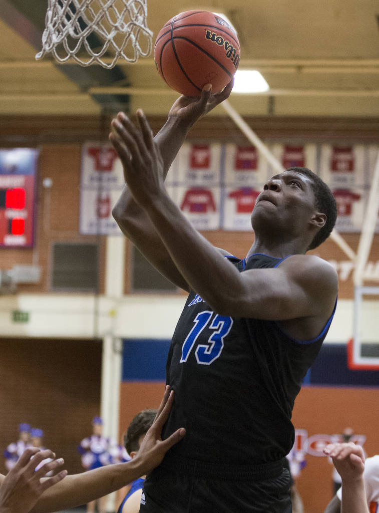 Desert Pines junior Darnell Washington (13) shoots a jump hook over Bishop Gorman defenders in the fourth quarter during the Southern Nevada boys basketball championship game on Monday, Feb. 25, 2 ...