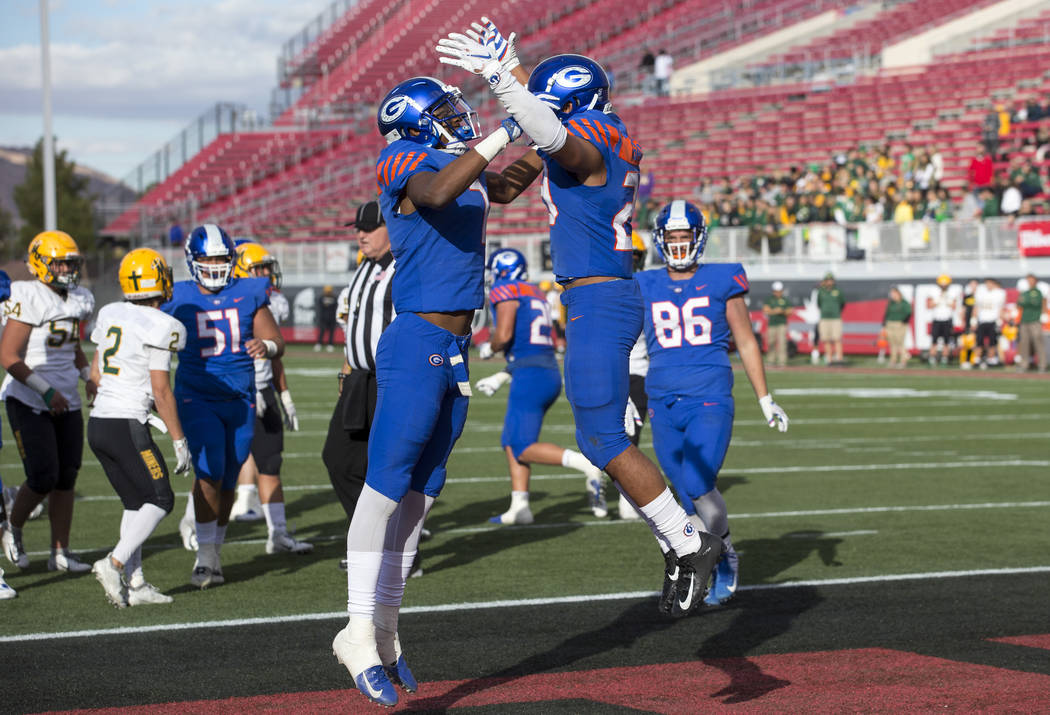 Bishop Gorman running back Amod Cianelli (23), right, celebrates his touchdown with Donovan Smith (7) during the second half of the NIAA high school football championship game against Reno's Bisho ...