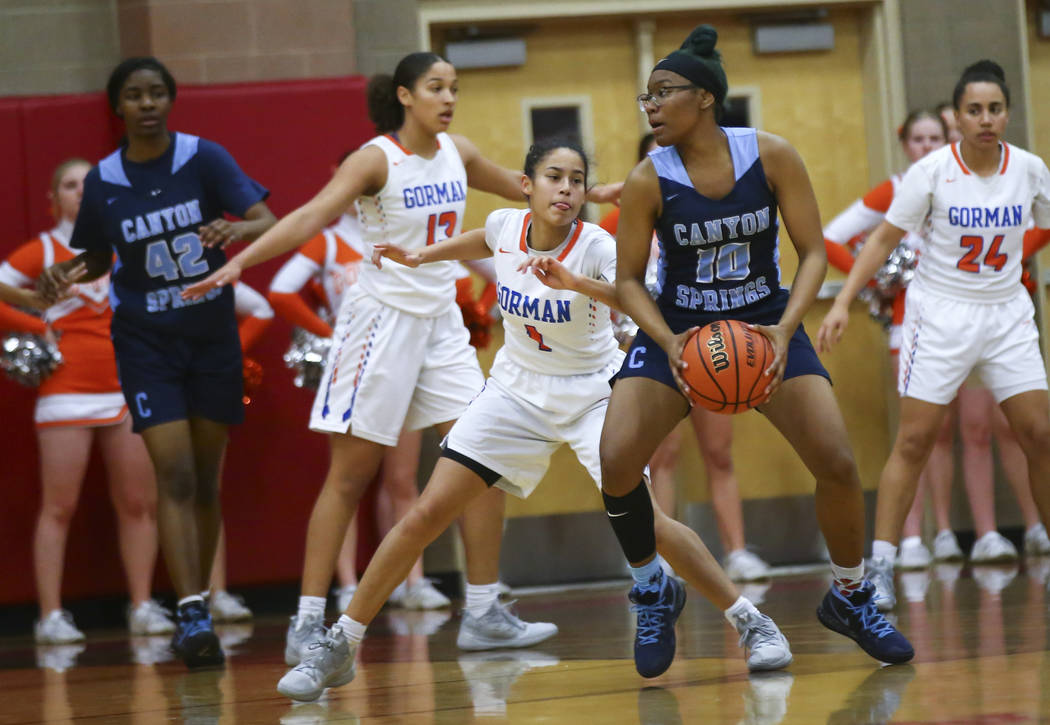Canyon Springs' Sydnei Collier (10) moves the ball around Bishop Gorman's Caira Young (1) during the first half of a Class 4A state girls basketball quarterfinal game at Arbor View High School in ...