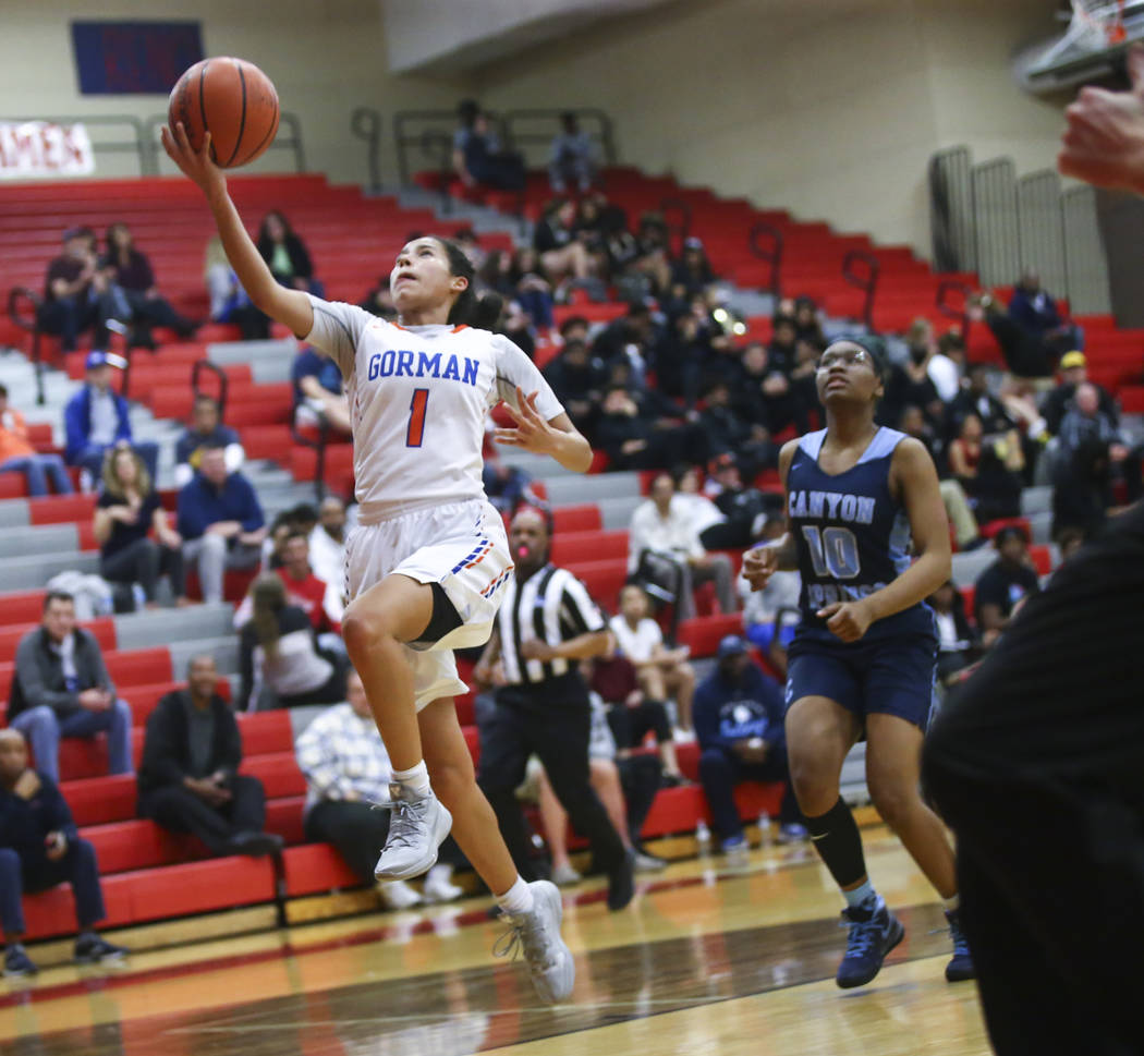 Bishop Gorman's Caira Young (1) goes to the basket past Canyon Springs' Sydnei Collier (10) during the first half of a Class 4A state girls basketball quarterfinal game at Arbor View High School i ...