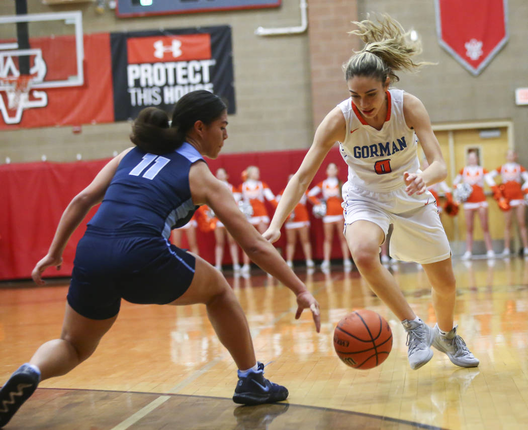 Bishop Gorman's Izzy Westbrook (0) and Canyon Springs' Jeanette Fine (11) chase after a loose ball during the first half of a Class 4A state girls basketball quarterfinal game at Arbor View High S ...