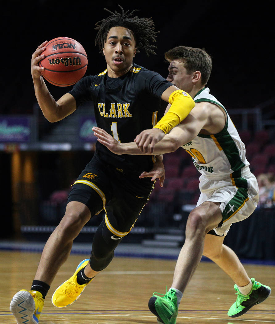 Clark's Frankie Collins (1) runs with the ball while being guarded by Bishop Manogue's Cort Ballinger (20) during the first half of a Class 4A state boys basketball semifinal game at the Orleans A ...