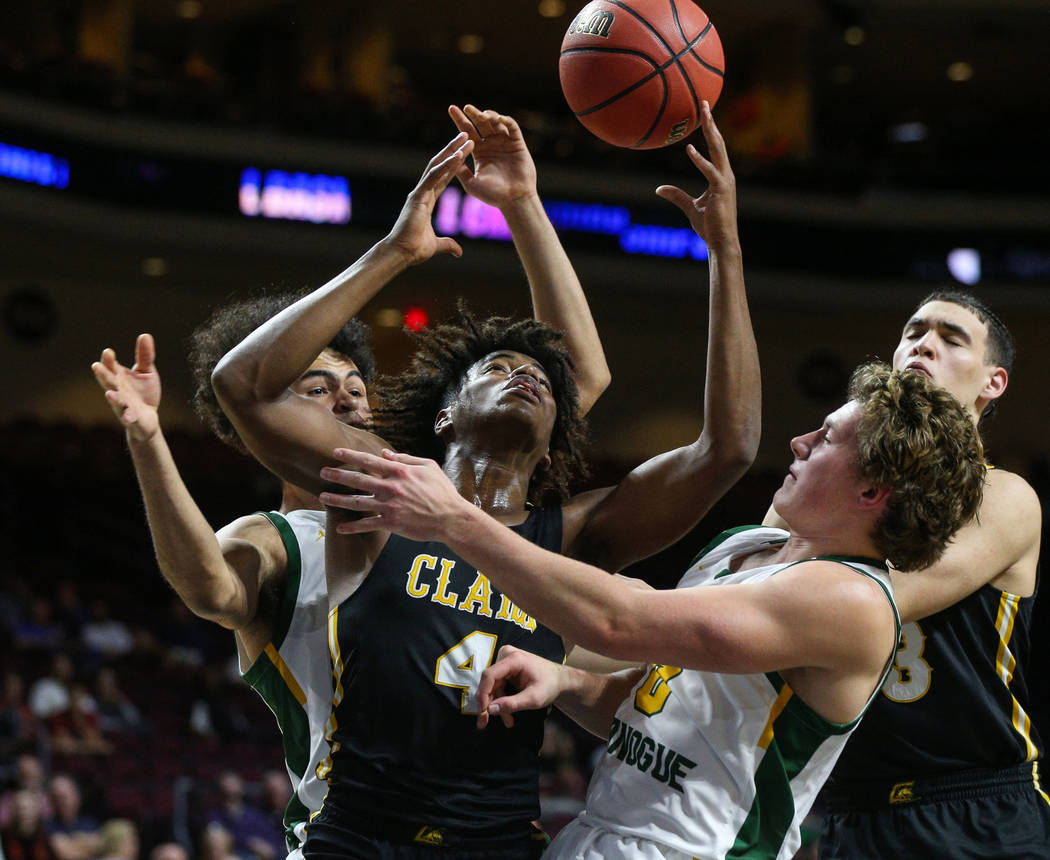 Clark's Carlos Allen (4) reaches up for the ball while being guarded by Bishop Manogue's Curtis Luckadoo (4) and Brayden Debruin (0) during the first half of a Class 4A state boys basketball semif ...