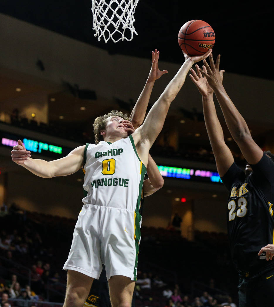Bishop Manogue's Brayden Debruin (0) reaches up for the ball over Clark's Cameron Kimble-Carey (12) and Antwon Jackson (23) during the second half of a Class 4A state boys basketball semifinal gam ...