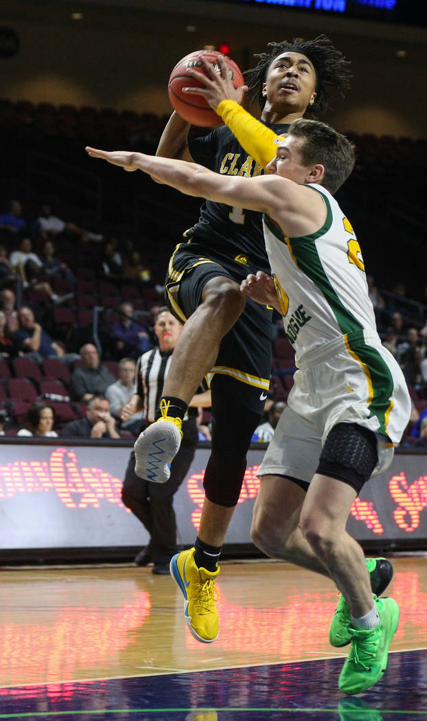 Clark's Frankie Collins (1) jumps up to take a shot while being guarded by Bishop Manogue's Cort Ballinger (20) during the first half of a Class 4A state boys basketball semifinal game at the Orle ...