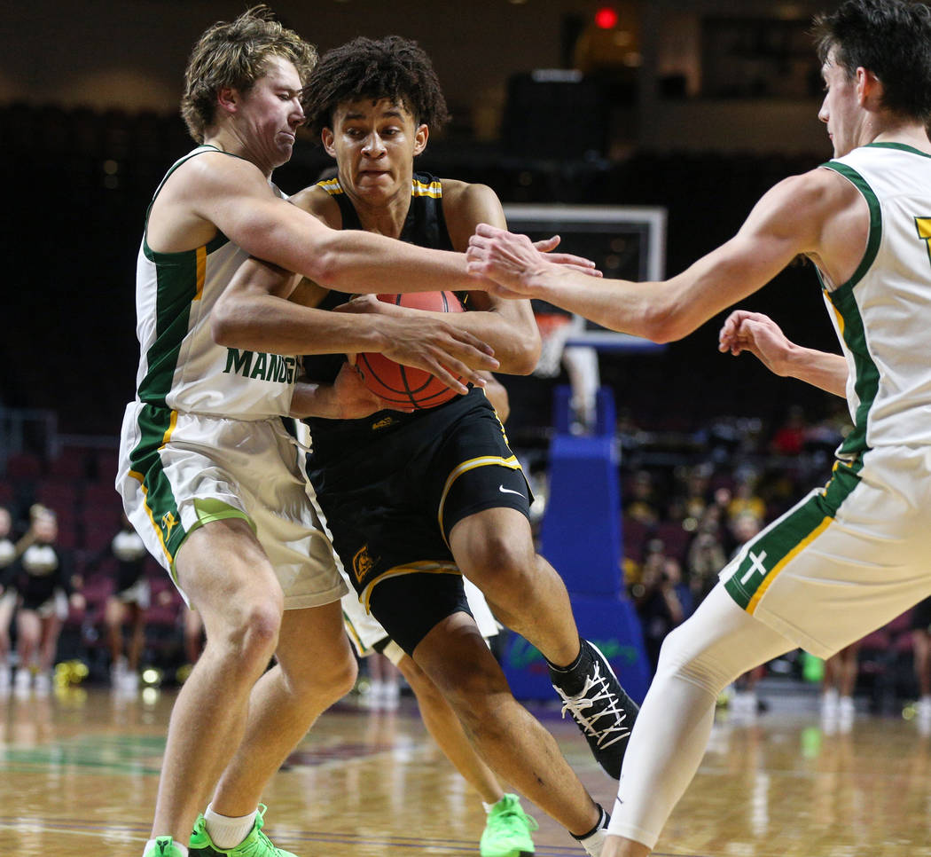 Clark's Jalen Hill (21) protects the ball from Bishop Manogue's Brayden Debruin (0) and Kolton Frugoli (10) during the first half of a Class 4A state boys basketball semifinal game at the Orleans ...